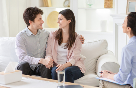 Reconciliation between spouses, mutual understanding. Professional therapist and happy couple in office, free space