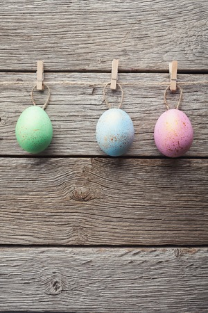 Easter quail eggs attach to rope with clothes pins on grey wooden background, copy space