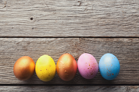 Colourful easter eggs in row on wooden background, top view, copy space Stockfoto