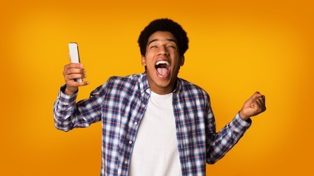 Excited student with phone celebrating victory over yellow studio background Imagens - 120395923