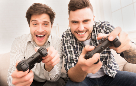 Gamers. Happy guys playing video games, having fun at home
