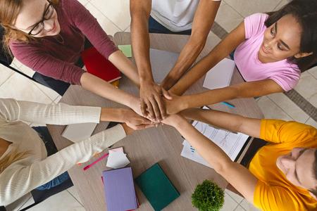 Gemischtrassige Teenager, die sich in Zusammenarbeit die Hände zusammenschließen, ein gemeinsames akademisches Projekt vorbereiten, Draufsicht