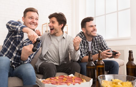 Excited men playing video games, having fun at home Archivio Fotografico
