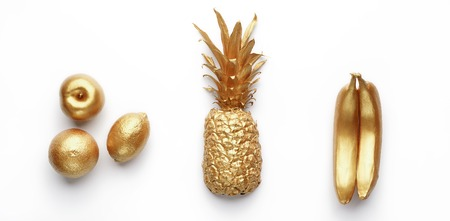 Golden tropical fruits in row on white background