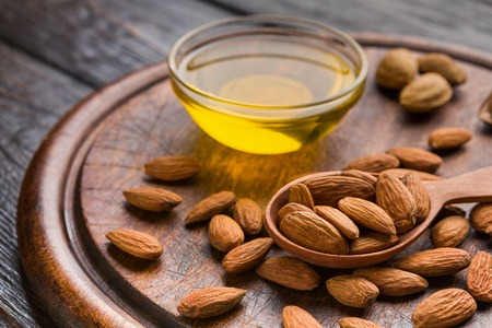 Almond oil in bowl and almonds on round wooden board. Natural skin care concept