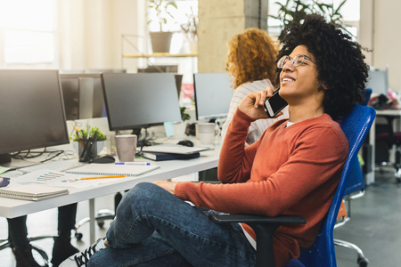 Young african american man talking on phone in modern coworking office, free space