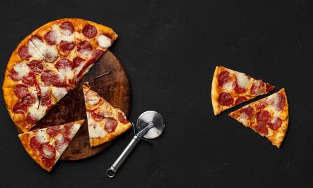 Geschnittene Peperoni-Pizza auf Schneidebrett mit Cutter in der Nähe, Ansicht von oben Standard-Bild
