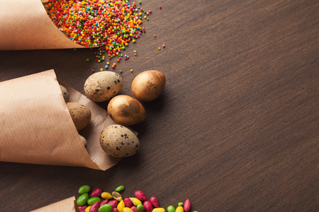 Quail eggs and colourful candies in craft paper cornets