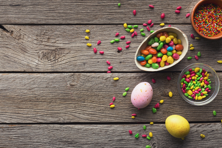 Easter eggs and scattered colorful candies on wooden background, copy space