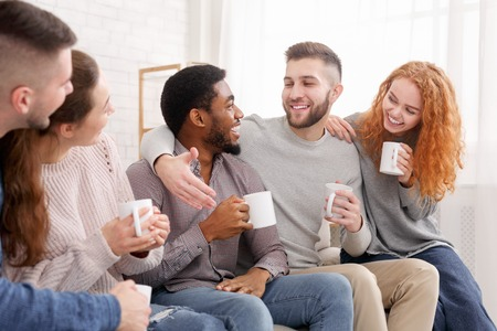Cheerful friends drinking coffee and enjoying their company, meeting at home