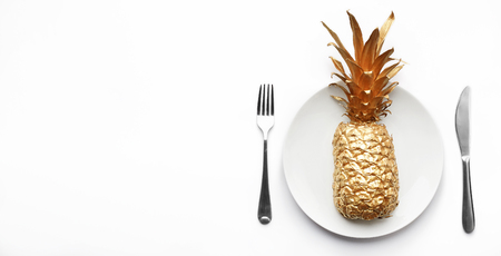 Golden pineapple served on plate on white background, copy space. Vegan nutrition concept 스톡 콘텐츠