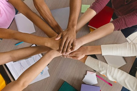 Friendship and teamwork. International college students stacking hand together, top view