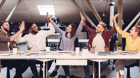Unity and teamwork. Designers giving high fives to each other in office