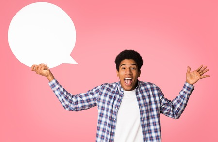 Hey, great idea. Happy african-american guy holding blank speech bubble, pink background
