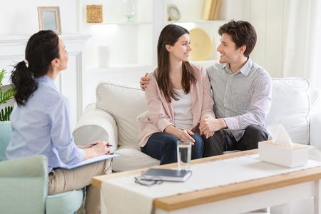 Solving problems in relationships. Happy couple at successful therapy session with family psychologist, sitting on sofa and embracing, free space