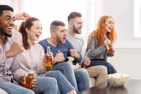 Cheering for favourite team. Friends watching match and shouting at home
