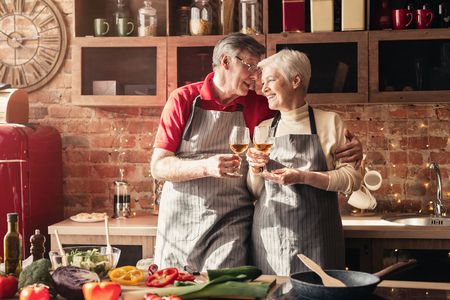 Cheers, dear. Cheerful senior man and woman clinking with wine glasses in kitchen interior