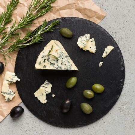 Blue cheese on black board, olives and herbs over concrete background, top view