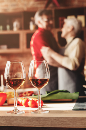 Senior couple in love dancing on their anniversary, celebrating with wine in kitchen, free space Reklamní fotografie
