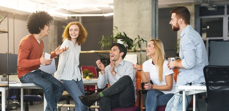 Friendship at workplace. Diverse millennial people having good talk at coworking space, panorama Stock Photo