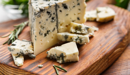Chopped blue cheese and rosemary sprigs on wooden cutting board 写真素材