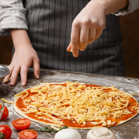 Chef sprinkling pizza with cheese on kitchen table, closeup, crop Stockfoto