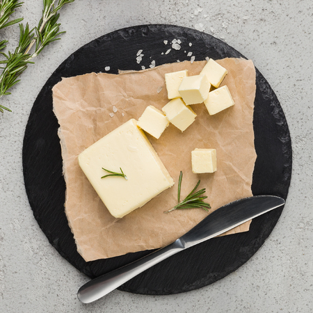 Chopped butter with rosemary in craft paper on wooden board over concrete background, top view. Homemade butter recipe mockup, copy space Imagens