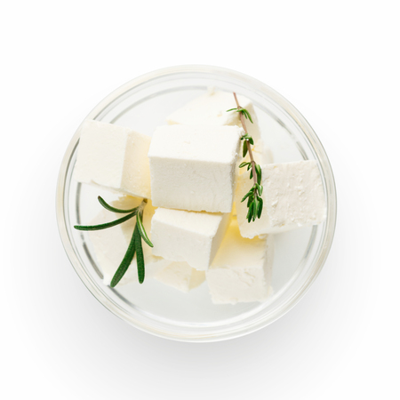 Feta cheese cubes and rosemary in glass bowl on white background. Greek salad ingredients concept