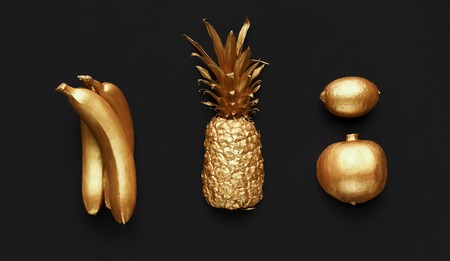 Set of golden fruits on black background, top view