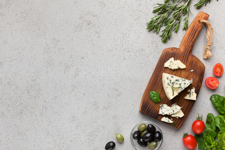 Blue cheese on wooden board, olives and herbs over concrete background, top view, copy space 写真素材