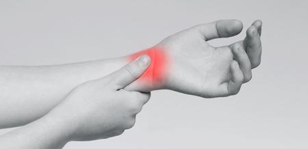 Carpal tunnel pain. Woman massaging painful wrist, monochrome panorama photo