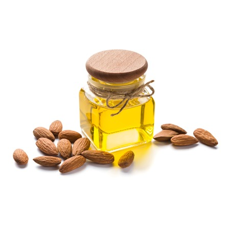 Almond oil in bottle and almonds scattered on white background, isolated. Stock Photo