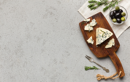 Blue cheese served on wooden board with olives and herbs over concrete background, top view, copy space. 写真素材 - 120803720