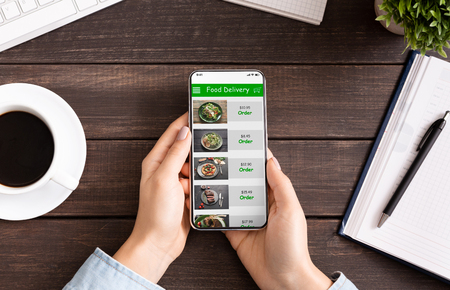 Takeaway service. Female hands scrolling smartphone screen with food delivery application, choosing meal for lunch, scrolling menu at workplace