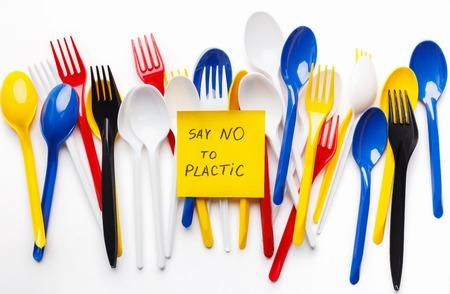 Tenedores y cucharas de plástico de un solo uso de colores sobre fondo blanco. No digas concepto de plástico
