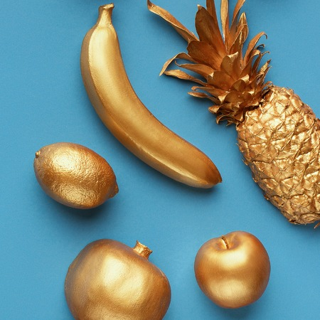 Golden fruits composition on blue background, top view. Crazy fruits concept Imagens