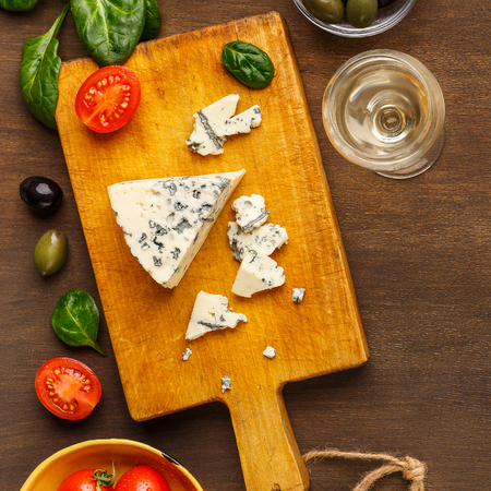 Blue cheese on board, olives and herbs on cutting board over wooden background, top view