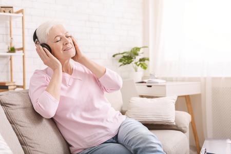 Neues Leben des Lieblingsbuches. Ältere Frau, die Hörbuch in Kopfhörern genießt, freier Raum