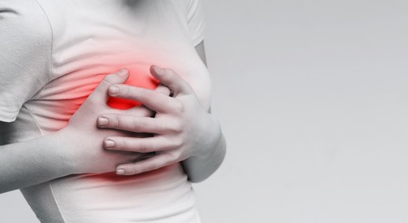 Breast pain. Woman suffering from painful feelings, clutching her boob, monochrome photo with red spot, panorama Фото со стока