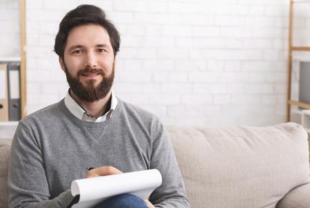Psicoterapeuta hombre barbudo escribiendo en el portapapeles y sonriendo a la cámara, sentado en la oficina, espacio libre