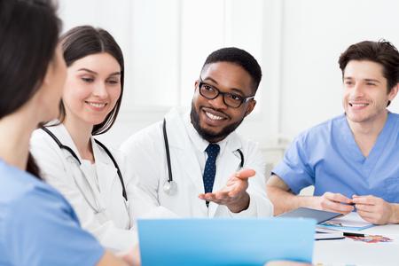 Équipe médicale multiraciale ayant une réunion avec un médecin, discutant des dossiers des patients