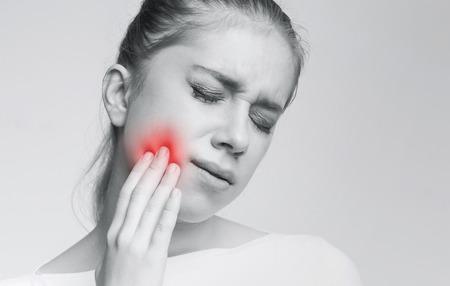 Problema dental. Mujer joven que sufre de dolor de muelas fuerte, foto monocroma con zona roja inflamada