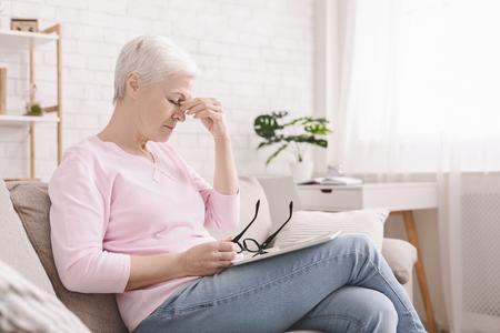 Problema de fatiga ocular. Mujer mayor molesta quitándose las gafas, que sufre de visión borrosa después de un largo uso de la tableta digital, espacio libre