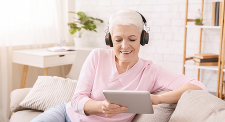 Mature gamer. Senior woman enthusiastically playing video games on digital tablet , wearing headphones at home, panorama, empty space Stok Fotoğraf