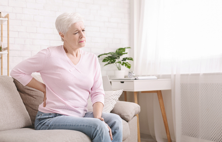Senior woman suffering from backache, sitting on couch and touching loin at home, empty space