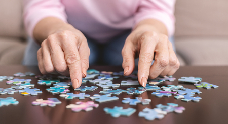 Senior woman hands doing jigsaw puzzle at home, panorama, close up