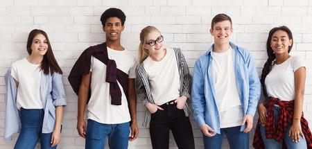 Estudiantes con estilo mirando a la cámara y posando sobre una pared blanca