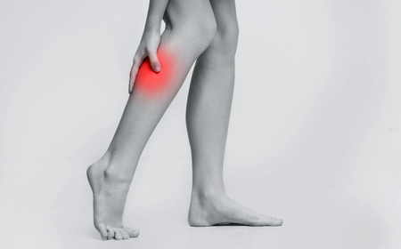Woman with injured calf, massaging painful leg muscle, black and white photo with red sore spot