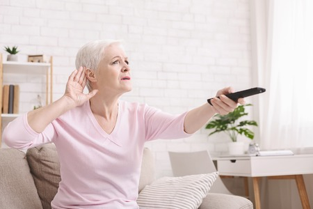 Senior woman cupping her hand behind ear to hear better to the television, making sound louder, empty space