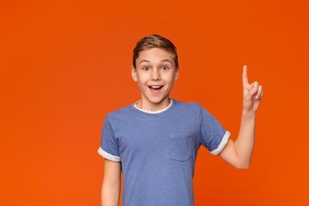 Emotional teen boy having idea, pointing finger up, got problem solution, orange studio background